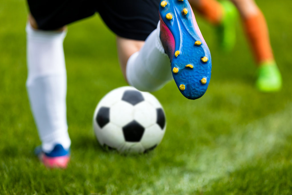 Soccer Kick. Footballer Kicking Ball on Grass Pitch. Football Soccer Player Hits a Ball. Soccer Boots Close Up
