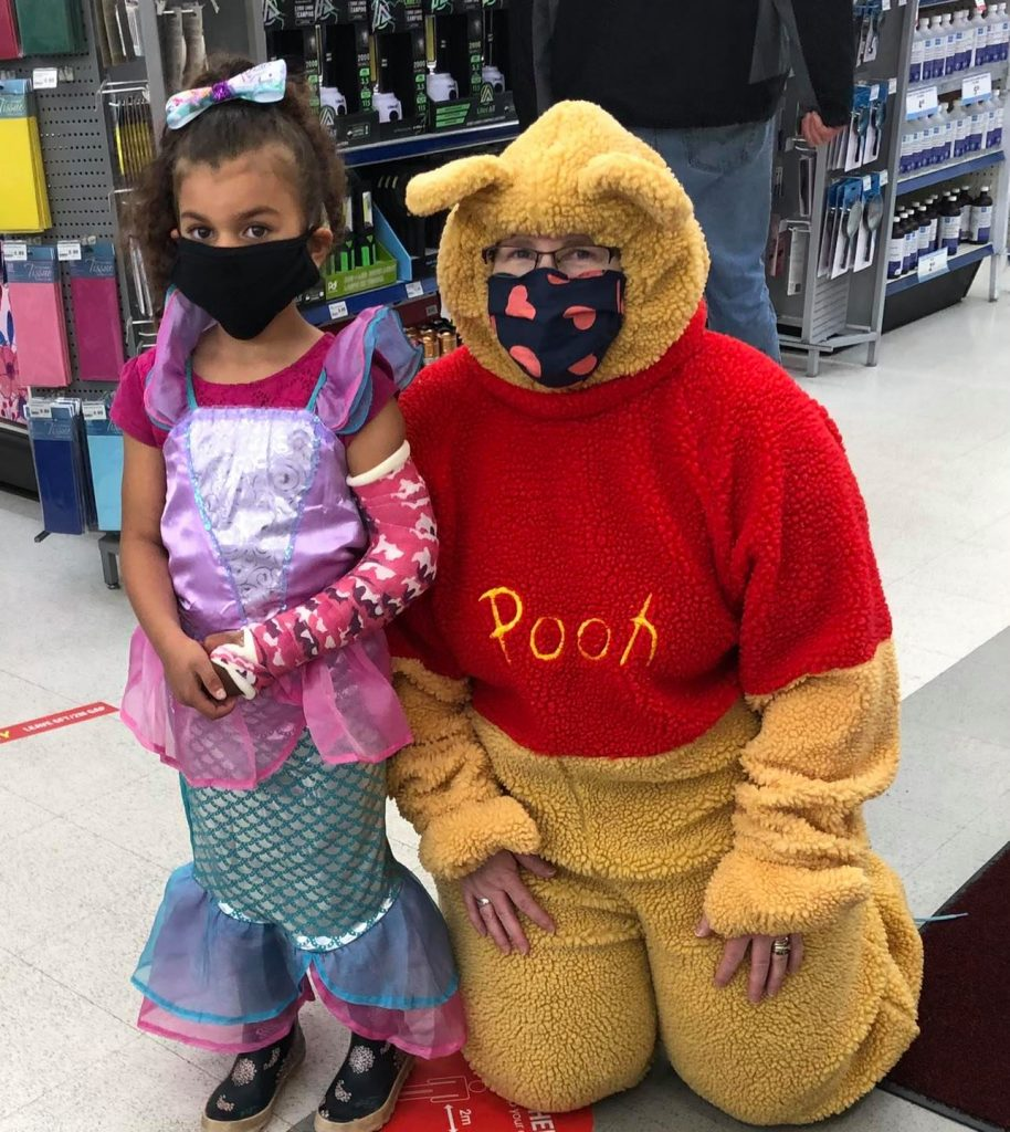 Young girl with broken arm dons princess outfit and stands next to store clerk dressed up as Winnie the Pooh