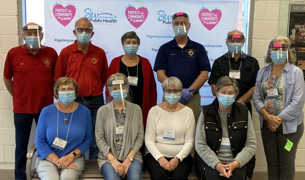 A shift of volunteers for the SWPH-led St. Thomas Mass Immunization Clinic assembled before returning to help at the busy hall. Front row, from left: Diane Somerville, Judy Holtby, Terry Collins, and Alanah Mitchell; back row: Otis Clifton, Case Hoffer, Pat West, Harald Schraeder, Gary Long and Sue Bowie. Some shown, including Mr. Hoffer, are members of the local Knights of Columbus service club, which has been coordinating a volunteer team to assist at the clinic regularly since March. (AE/contributed by SWPH)